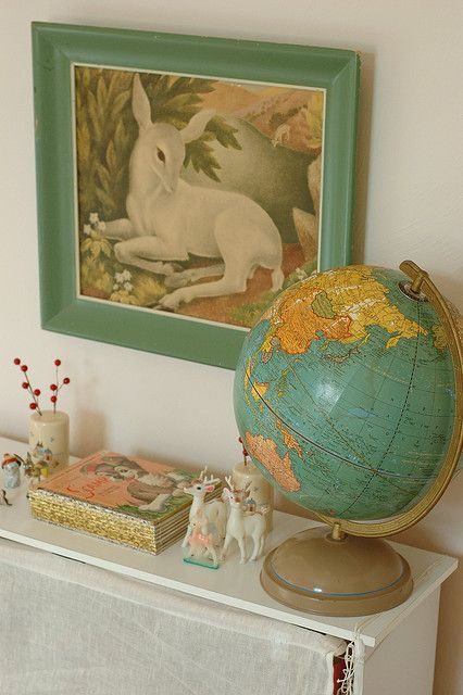Framed kitschy deer print and a bright vintage revolving globe.