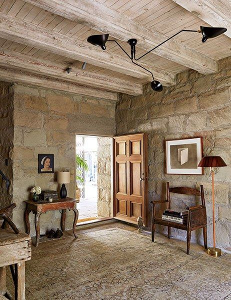 This Tuscan-style villa in Santa Barbara, constructed in the 1930s by Wallace Frost, is set amid olive trees and overlooks the Pacific Ocean. In the foyer, the light fixture by Serge Mouille is a modern counterpoint to the stone walls, rustic beamed ceiling, and wood furnishings, including a baroque side table.