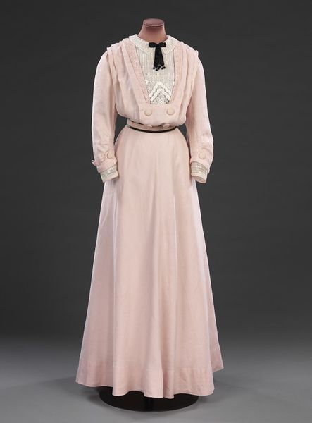 (ca. 1908) This pink linen dress bears no makers label, but is likely to be made by a high end dressmaker of the sort employed for less important and less costly gowns. The centre front of the skirt is cut on the cross, giving a graceful hang to the fabric and the dress is trimmed with cotton braid and embroidered striped net. The gilet front adds to the fashionable pouched bodice shape of the Edwardian silhouette. A relatively understated garment, it was probably worn for summer activities.