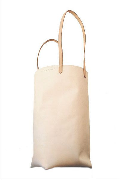 Paper bag-inspired tote in smooth, buff leather with tan shoulder straps. Spacious, single interior compartment. Raw leather interior. Handcrafted in...