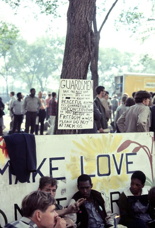 Protesters Seated In Front Of A Makelovenotwar Sign During The