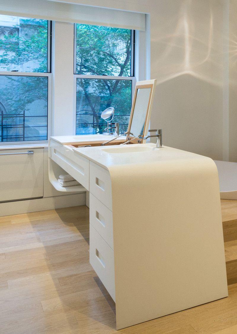 A sculptural bathtub was sunken into a raised platform in this New ...