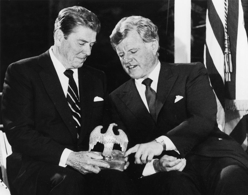 Senator Edward Kennedy talks with President Ronald Reagan, left, on June 24, 1985, as they look over an American Eagle that graced President John F. Kennedy's desk during a fund raising event for the John F. Kennedy Memorial Library at McLean, Virginia. (AP Photo/Charles Tasnadi) #