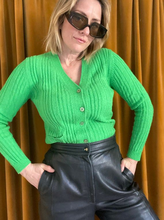 Gorgeous little vintage cardigan by MYER. Bright kelly green.Made in the 1970s or 1980s Made in Hong KongAcrylic Nylon blend . Not itchy or scratchy . Fabric has some stretch  Five buttons on front all intact Good vintage condition. There was some pilling which i have removed with my machine but overall the fabric has no holes or pulls.   MAKERS LABEL – MYER - Made in Hong KongSIZE LABEL - 14 but smaller in modern sizingFABRIC - Acrylic/Nylon blend. Vintage garments are one-of-a kind and may sho
