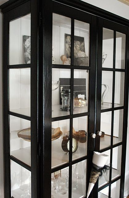 Black Wood And Glass Cabinet With White Wood Walls Dust