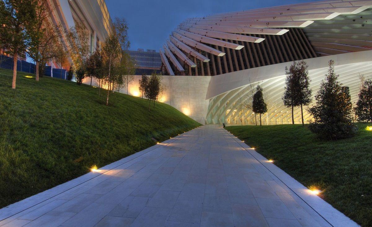 un viale e l'esterno di un edificio illuminati da faretti
