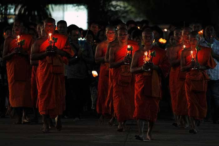 Buddhists-carry-candles-while-circling-a-temple-during-Makha-Bucha-Day-in-Nonthaburi-province,-on-the-outskirts-of-Bangkok
