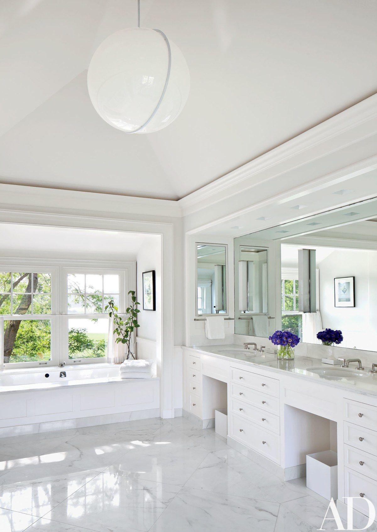 The adjoining marblefloored bath includes an acrylic pendant light