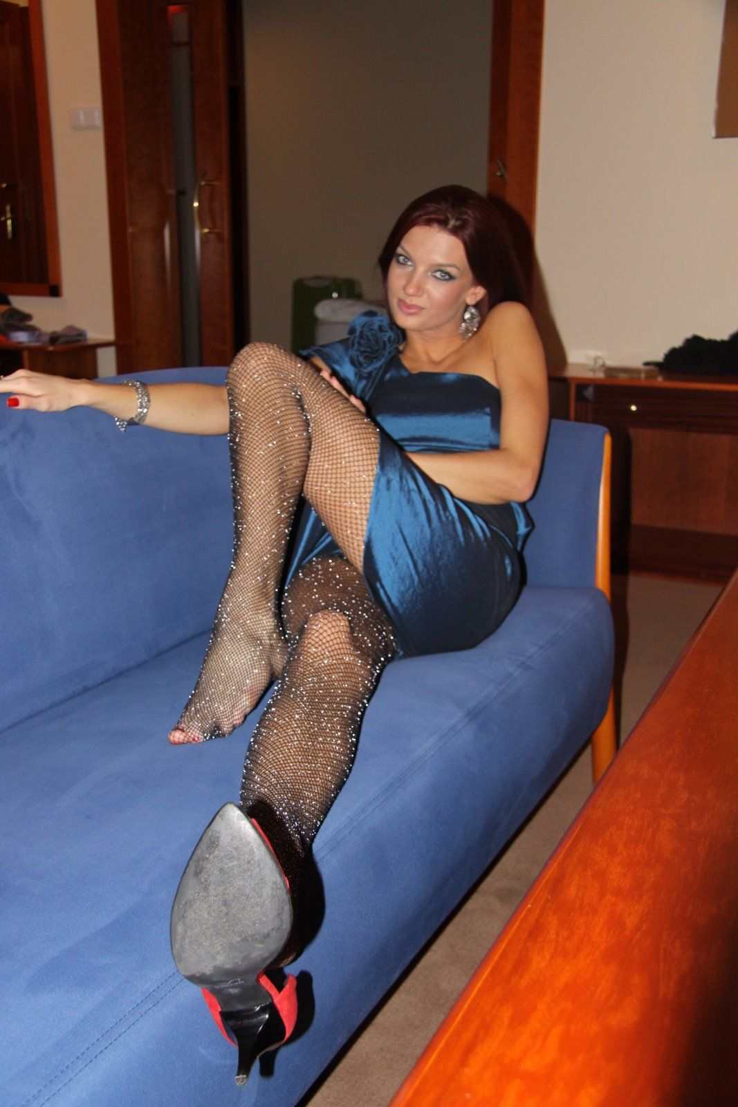 a classy woman is showing her glittering pantyhose and her satin