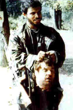 The head of a Serb, Blagoje Blagojevic, held by an Arab Saudi/Afghan 'Jihad' fighter in Crni Vrh, Bosnia, 1992.