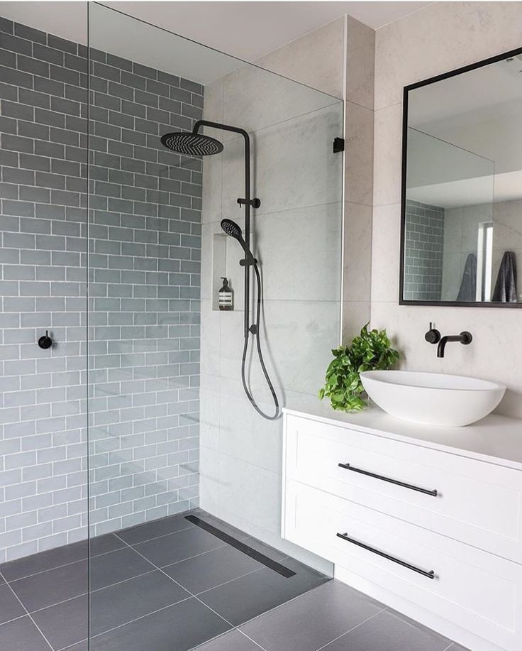 simple modern bathroom with white floating vanity, blue-gray subway tile, and large-format gray floor tile #bathroomtileshowers