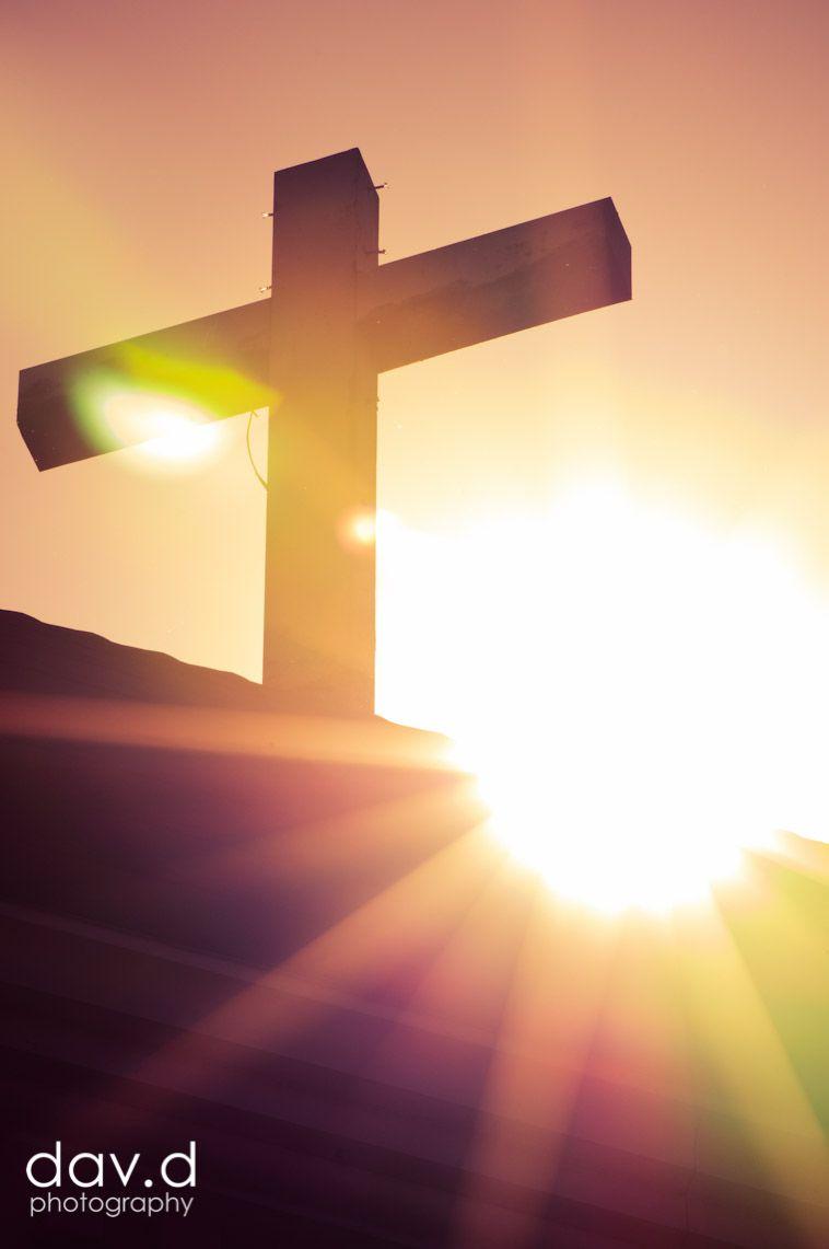 sun shining behind cross