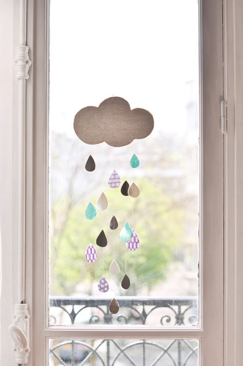 Idea for a mobile. Link just goes to main page and it's in French, won't do you much good. But it looks simple enough. Cut out shapes, glue raindrops onto string. Hang.