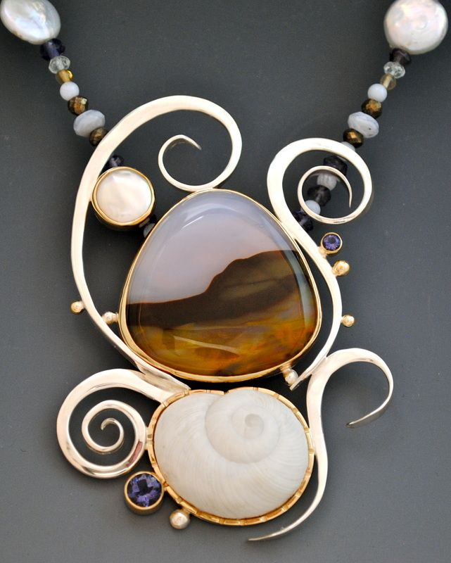 """California"" Necklace: Florida snail shell with isolates, pearls, blue lace agate, hematite, citrine & aquamarine. Barbara Umbel designs OOAK necklaces from sea urchins & seashells set in a combination of gold & silver. She uses traditional metalsmithing techniques to create abstract settings show the natural beauty of her beachcombing finds. Each piece is hand fabricated from 14k gold & sterling silver, & set with natural seashells, freshwater pearls, & gemstones…"