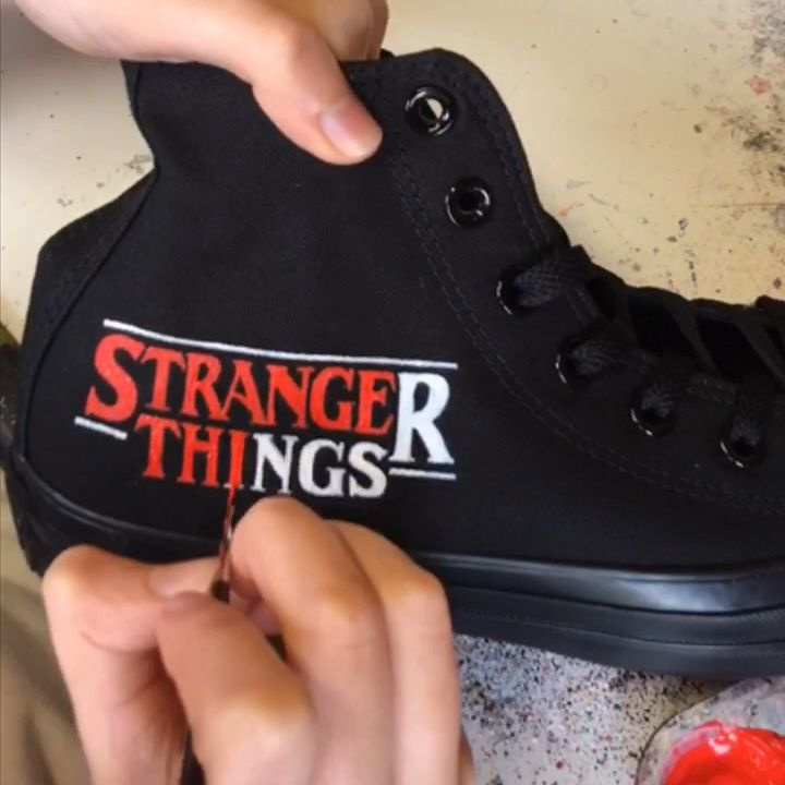 Plain black high top converse hand painted with the Stranger Things logo and Eleven design. #strangerthings #eleven #converse #sneakers #timelapse #painting #handpainted #paintedshoes #shoes #chucks #milliebobbybrown