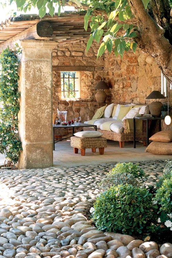 Terraza Rústica Con Suelo De Piedra Y Mobiliario En Mimbre