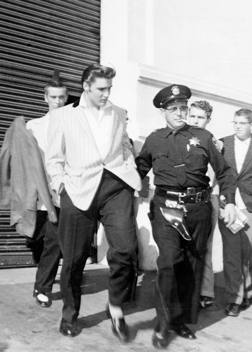Elvis, June 3, 1956. Oakland, CA. After the show, Presley stayed in the dressing room for almost half an hour until a squad of Oakland police could safely escort him to his car. As it was, 50 assorted fans managed to grab him and shouted and screamed as he drove away. To the few who were able to crash the police line and actually get near to him. Presley was casual, friendly and seemed to make it a habit to give each a quick peck on the cheek...
