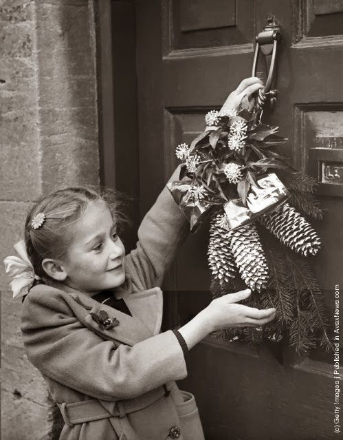 A young girl hangs a Christmas garland on the door of her cottage home at Northleach, Gloucestershire, in accordance with an old local custom. (Photo by Fox Photos/Getty Images). 24th December 1954.