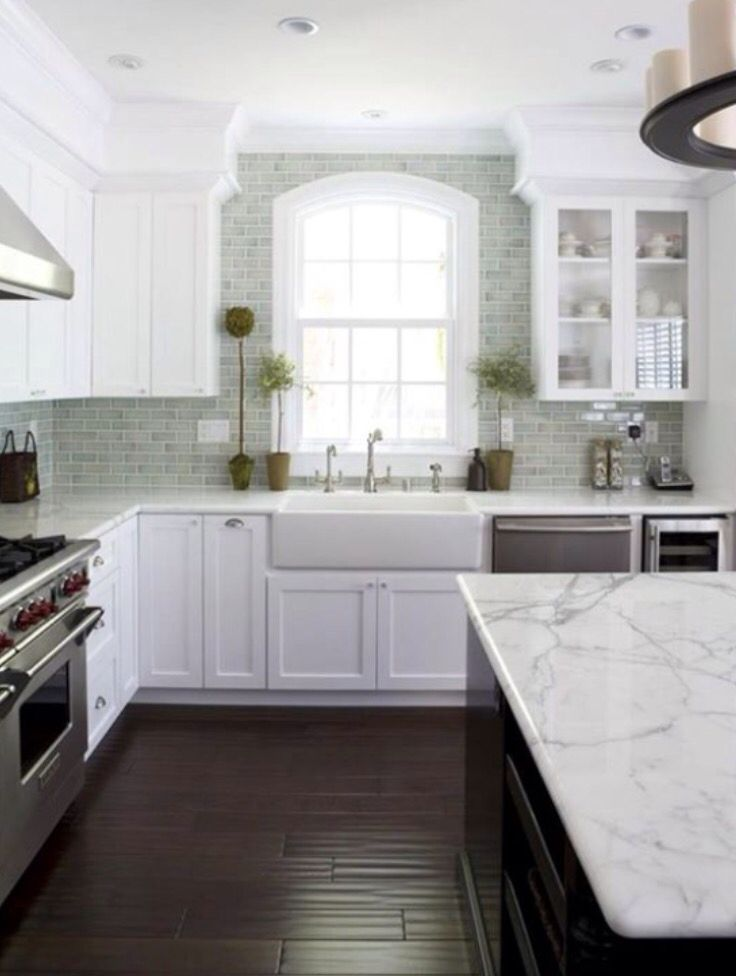 Kitchen dark floors white cabinets brick stacked backsplash