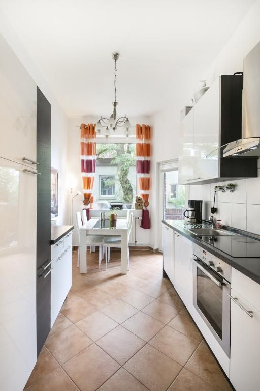 Modern eingerichtete Küche mit Vorhängen in orange und lila sowie