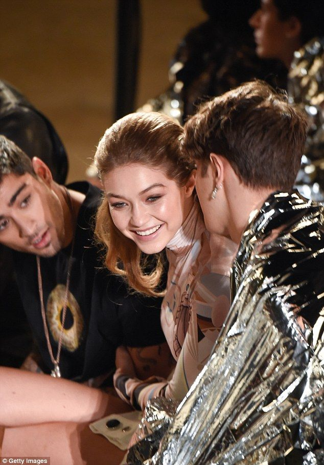 Chatting away:Zayn Malik appears to have not only won over his girlfriend Gigi Hadid but also her tight knit family as the couple were seen sitting alongside her 17-year-old brother Anwar at the Givenchy Paris Fashion Week show on Sunday night