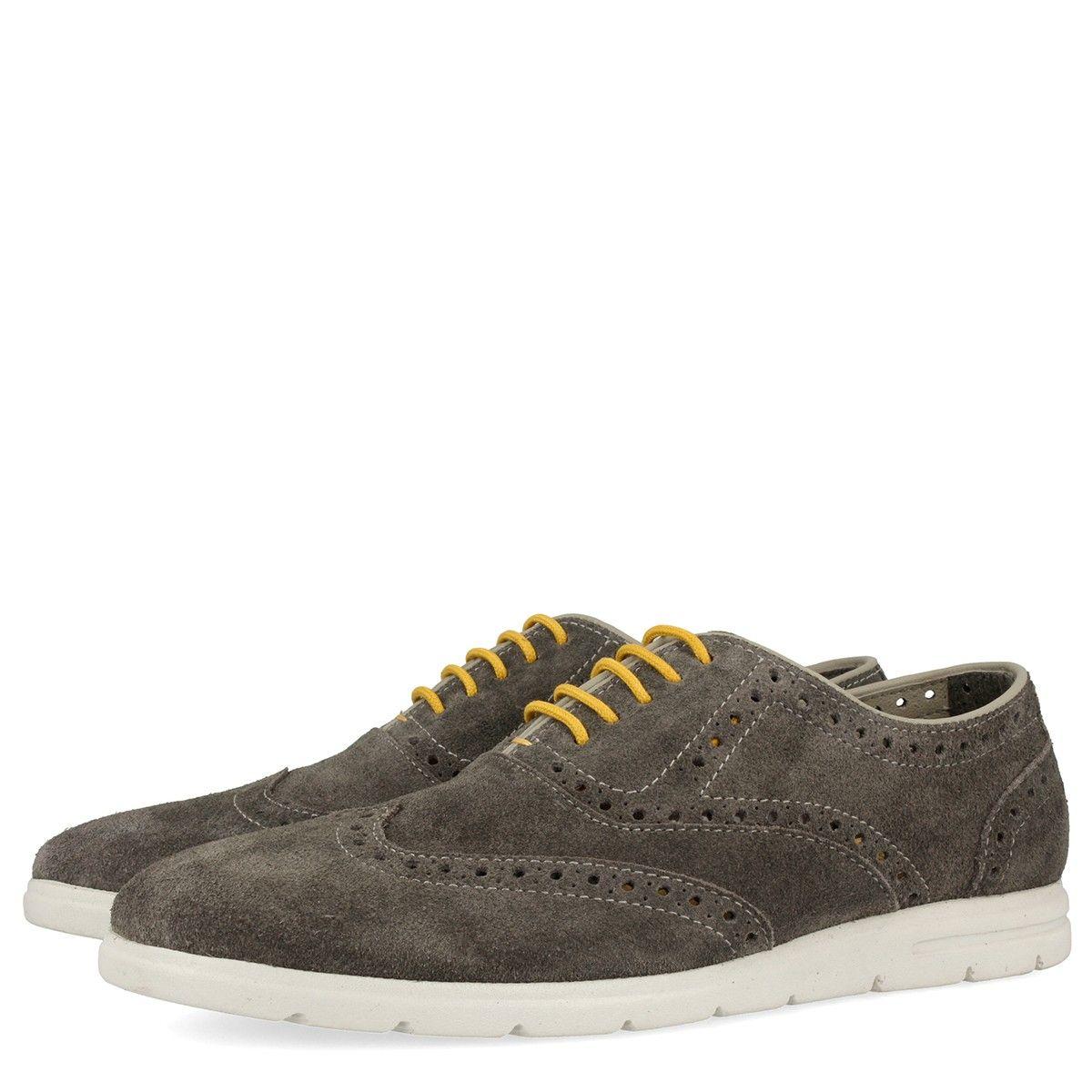 Zapatillas de piel gris estilo oxford. Detalle de cordones amarillos y suela blanca. Corte y forro en piel y plantilla de tejido.