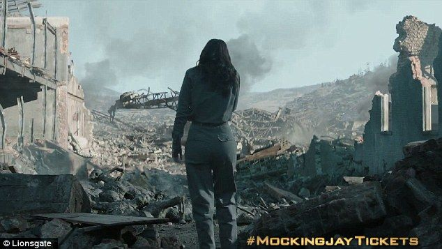 Surveying the damage: Jennifer Lawrence plays the heroine, who can be seen standing amongst the ruiins after a bomb  District 12