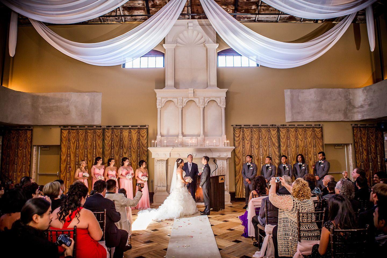 wedding ceremony light pink bridesmaids dressses stone fireplace