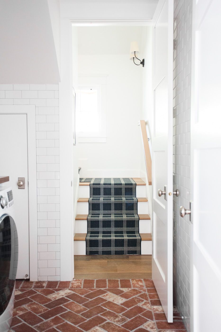 Brick herringbone floors and navy stair runner