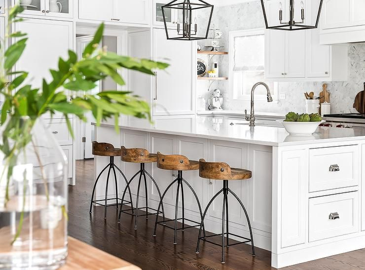 Four Arteriors Henson Counter Stools Sit At A White Kitchen Island Topped With Quartz Countertop And Finished Shaker Drawers