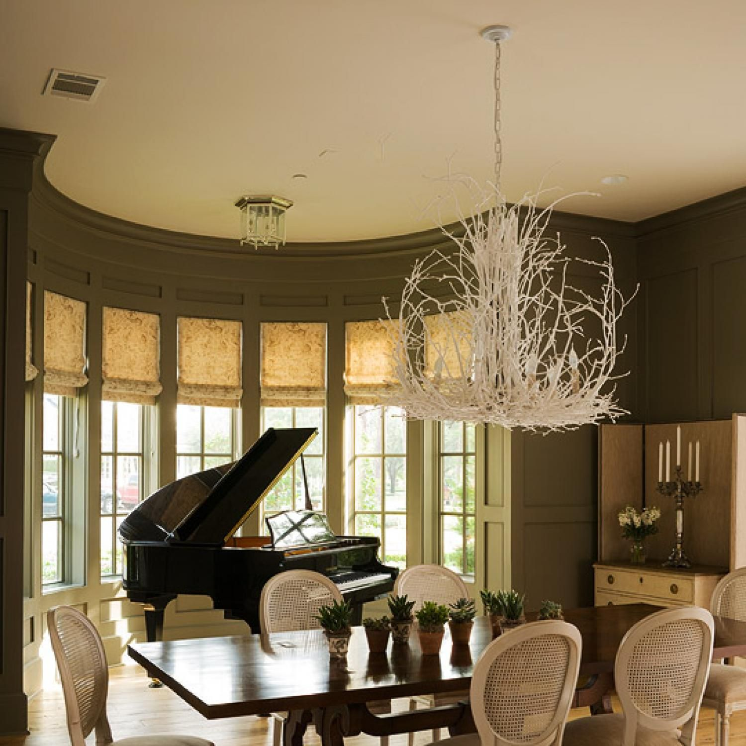Silhouetted against a demilune bay window a glossy black for Beautiful traditional dining rooms