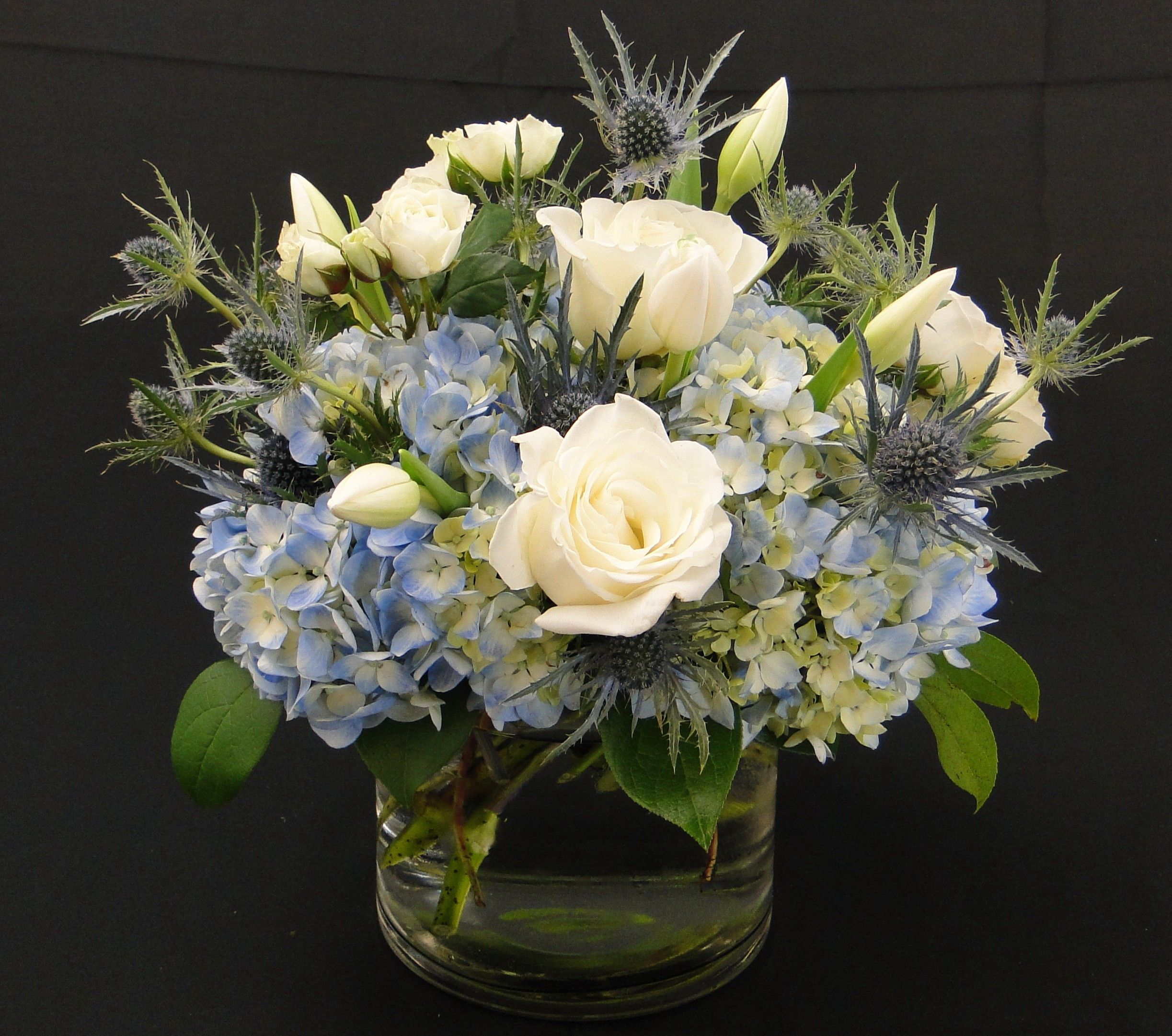 Cool Reflection-   A calming seaside gathering of soft blues, and sandy ivories using hydrangea, eryngium, roses and tulips to transport you another place. Cool Reflection White, Green, Blue PJ's Flowers & Events Tony Medlock