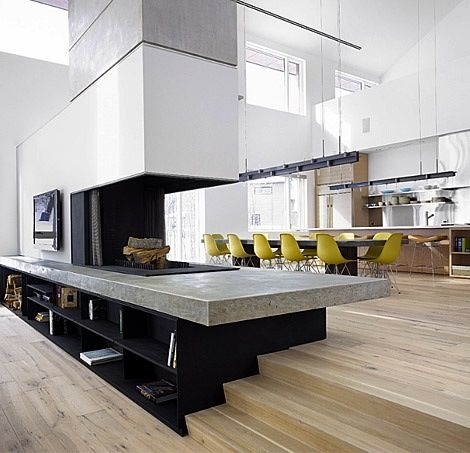 Open living spaces separated by fireplace