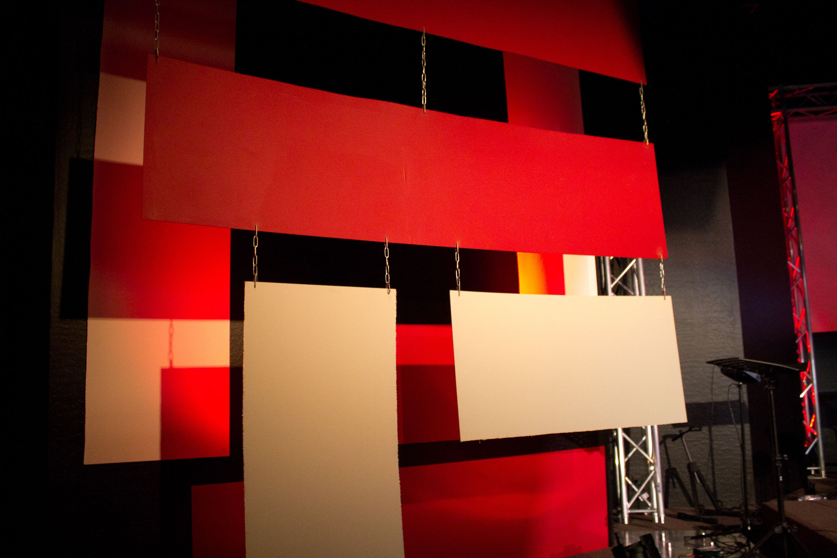 The white and red panels were cut out of masonite and hung with chain. The panels were front lit with traditional Par cans and 4 LED lights were using to provide some color on the walls behind the panels.