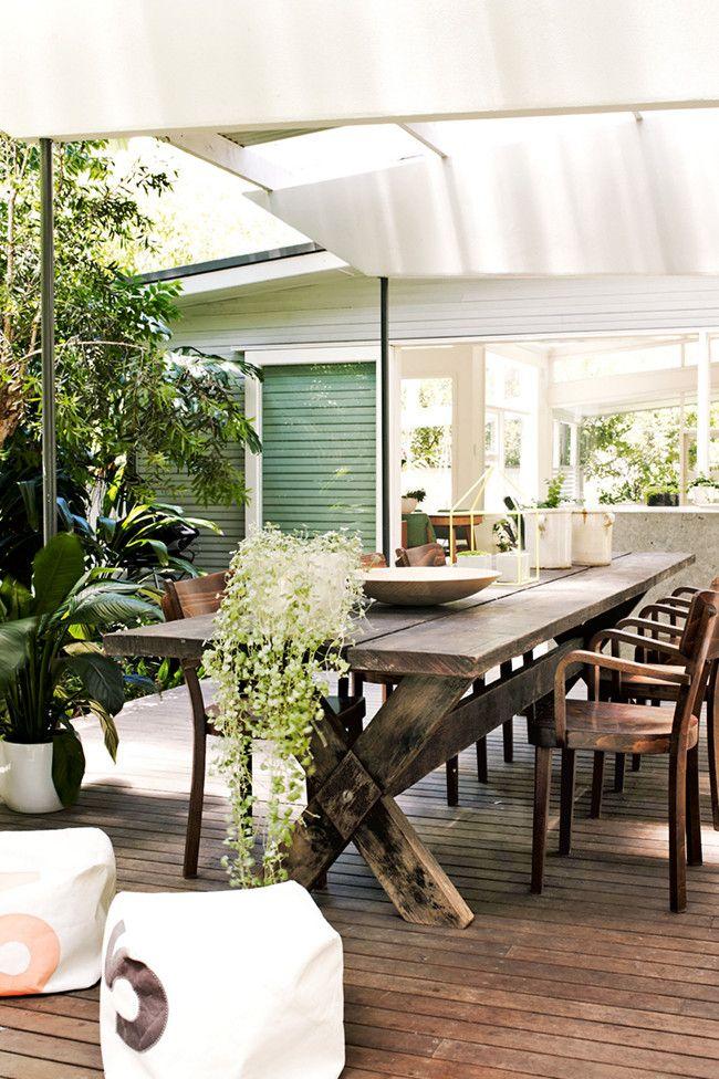 Le style vintage investit la terrasse en bois dune maison de campagne au sol de fines lames en teck accueillent une table en bois brut protégée du soleil