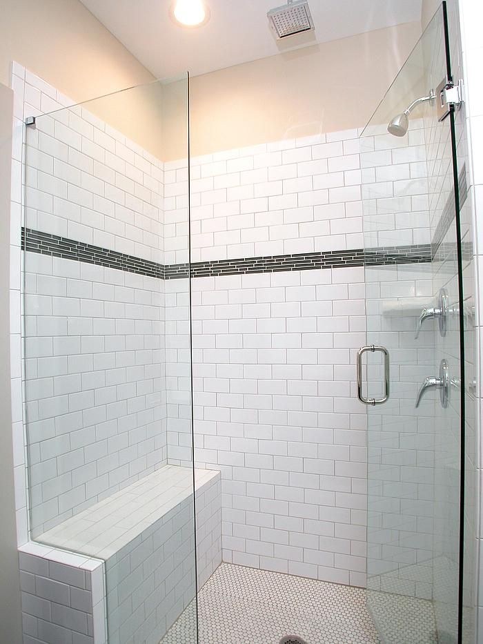 This walk in shower features white subway tile with glass ...