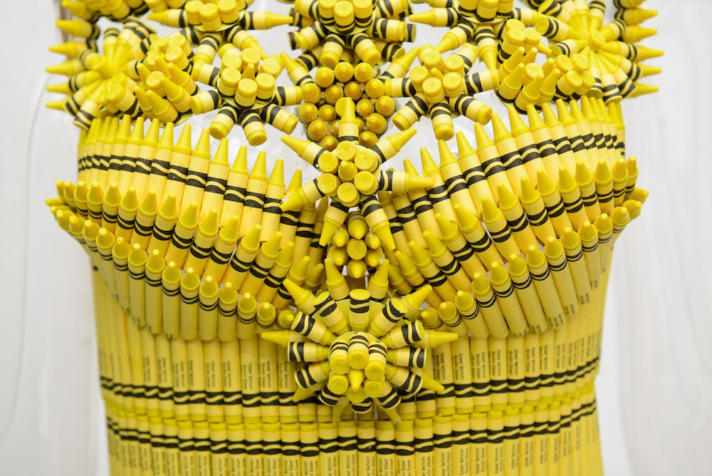 a bright yellow dress designed by Nanette Lepore, showcases a bustier of organized pinwheel crayon segments extending from the ornate neckline.