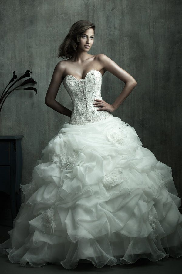 This strapless ball gown features a unique sweetheart neckline and corseted bodice embellished with embroidery and Swarovski crystals. The skirt has soft pick-up details accented with a flowers and feathers.