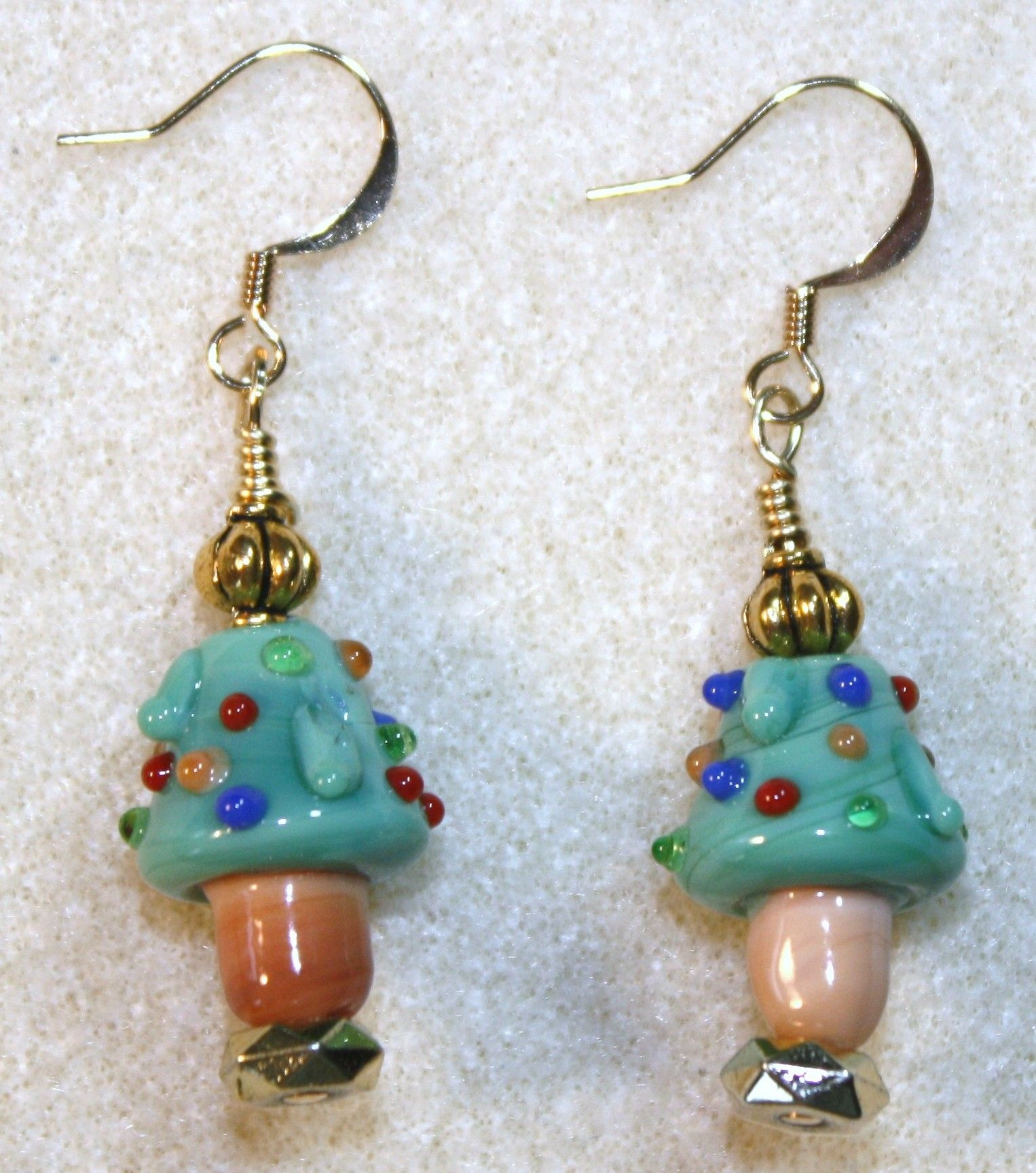 Handcrafted by Teal Palmetto, LLC. These tiny Christmas trees are all decorated for the holiday!  Glass Christmas tree focal beads are complemented with gold accent beads.  This pair has gold fish hook ear wires.  Price: $14.