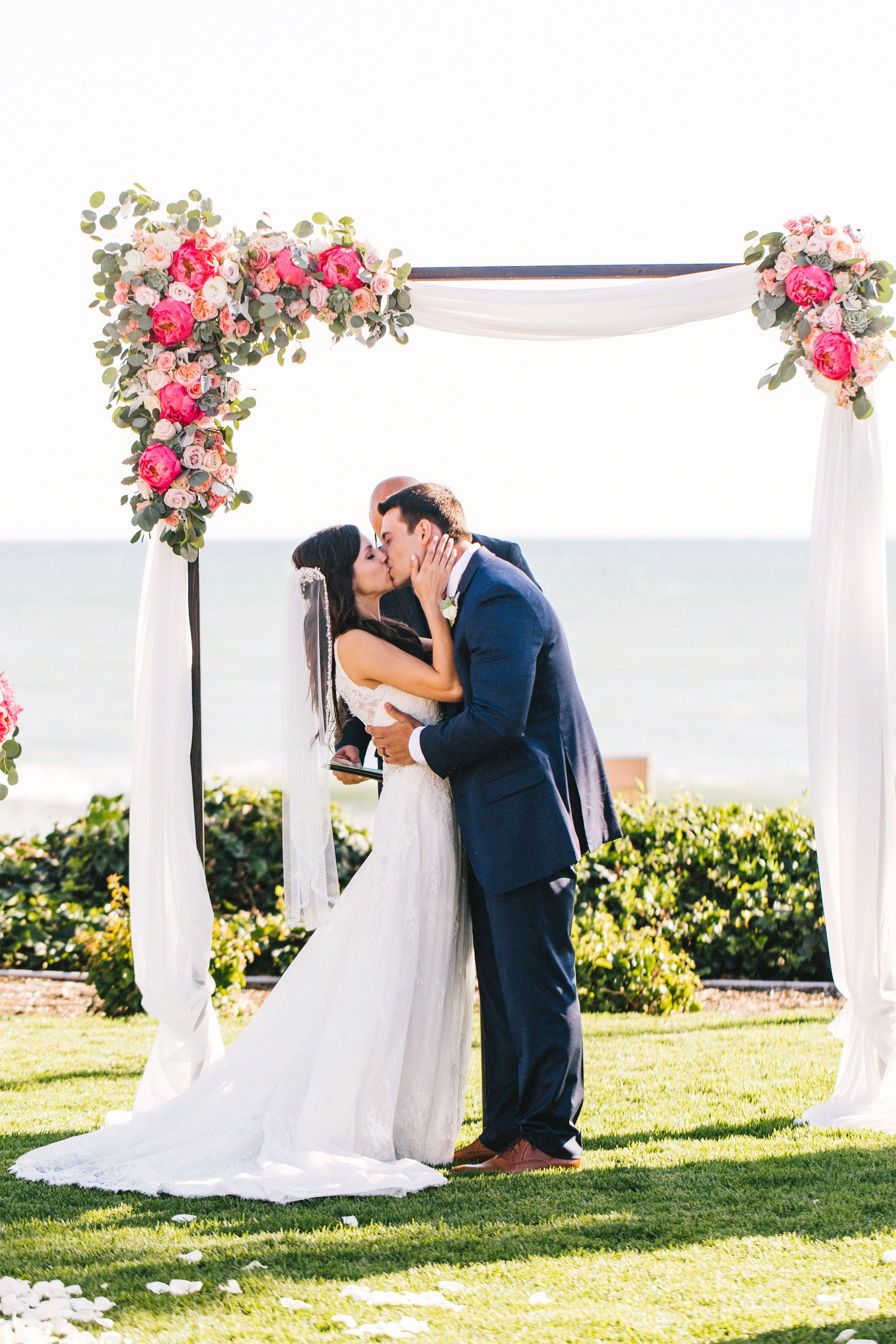 Asymmetrical wedding arch with fabric and peonies Beach