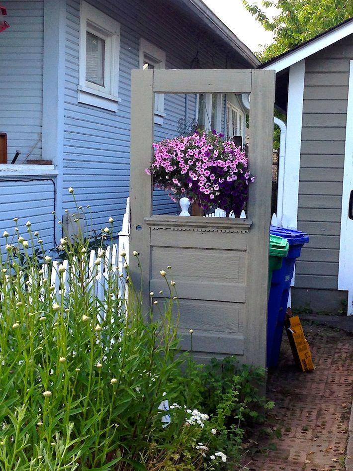 Repurposed Vintage Door Cleverly Hides Trash Cans Hide