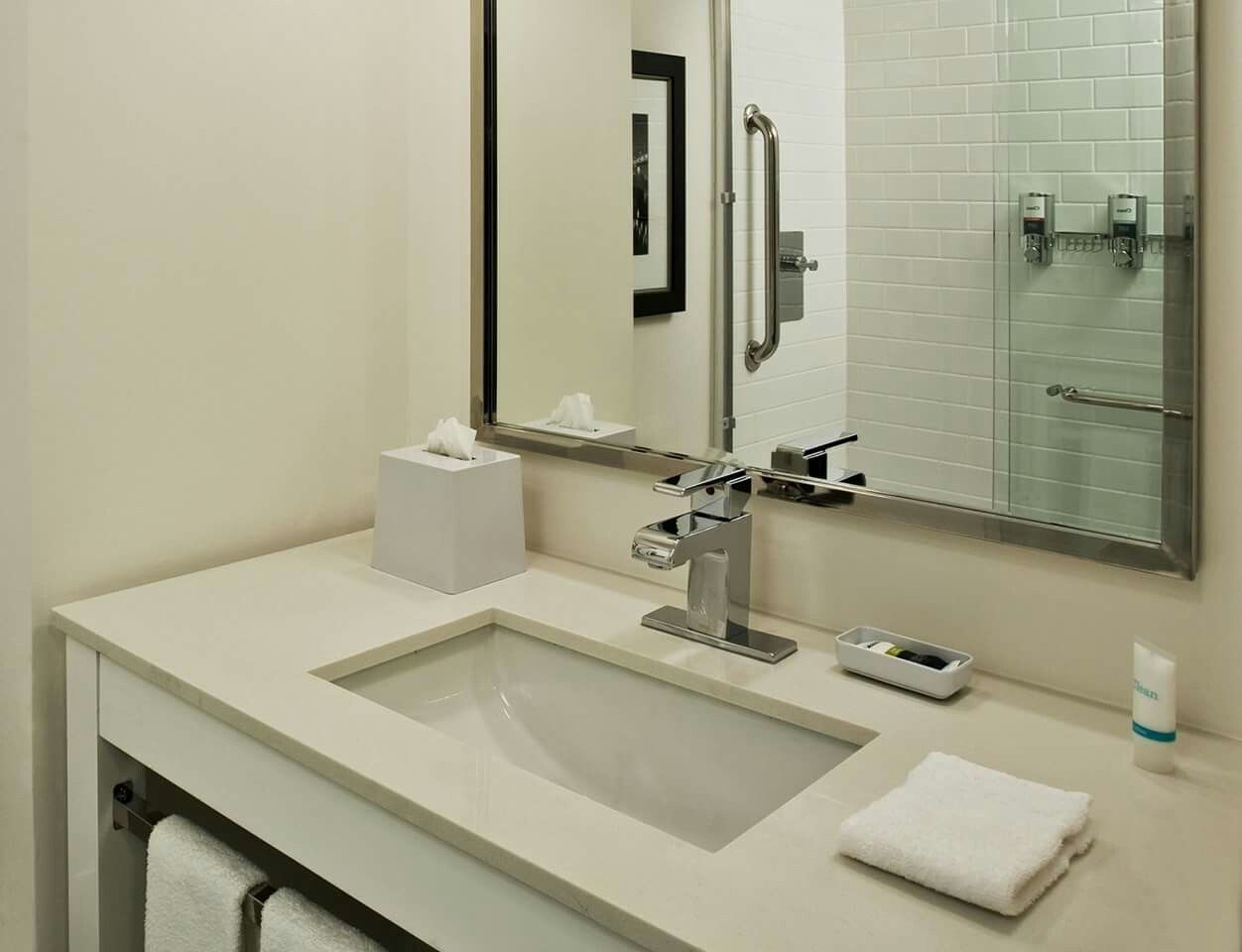 White engineered quartz top with white stained wood vanity base. Rectangular sink cutout and polished chrome metal faucet