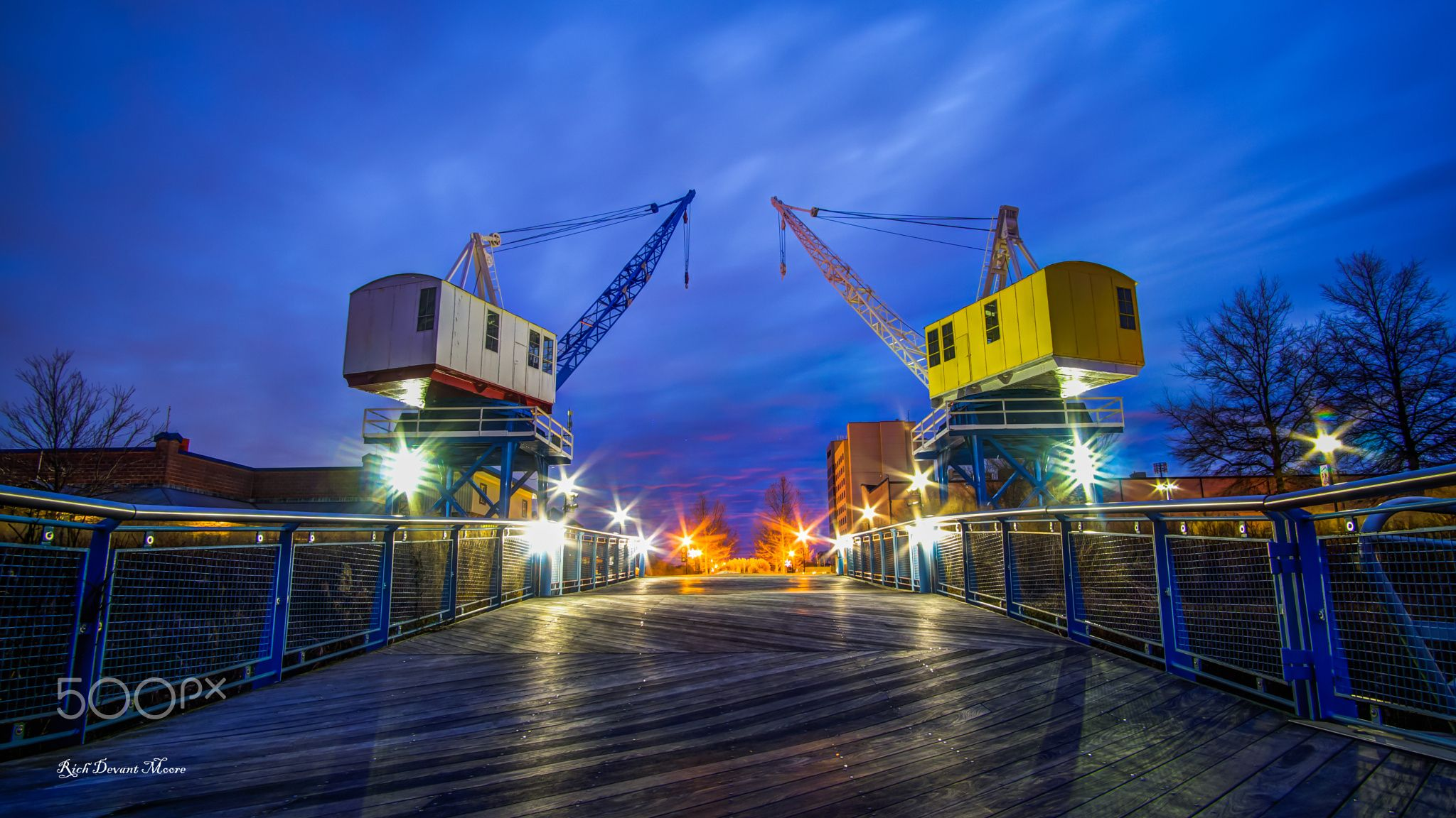 Crayon colored cranes between a blue hour sunset and a