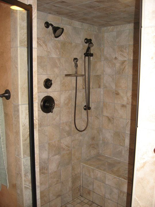 rebuilt shower with bench seat and a hand held shower head on slide bar for ease