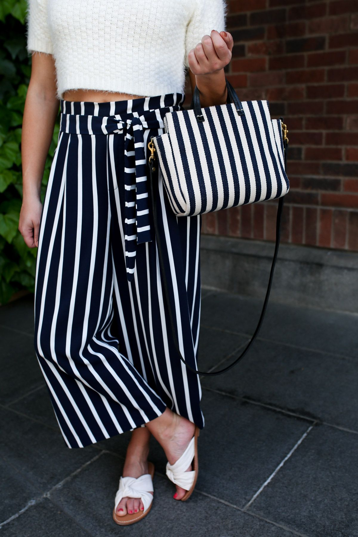 aebcfda128 Fashion blogger Jessica Sturdy styling a pair of Zara high-waisted striped  wide-leg pants with a pair of Soludos knotted slide sandals in Tokyo, Japan.