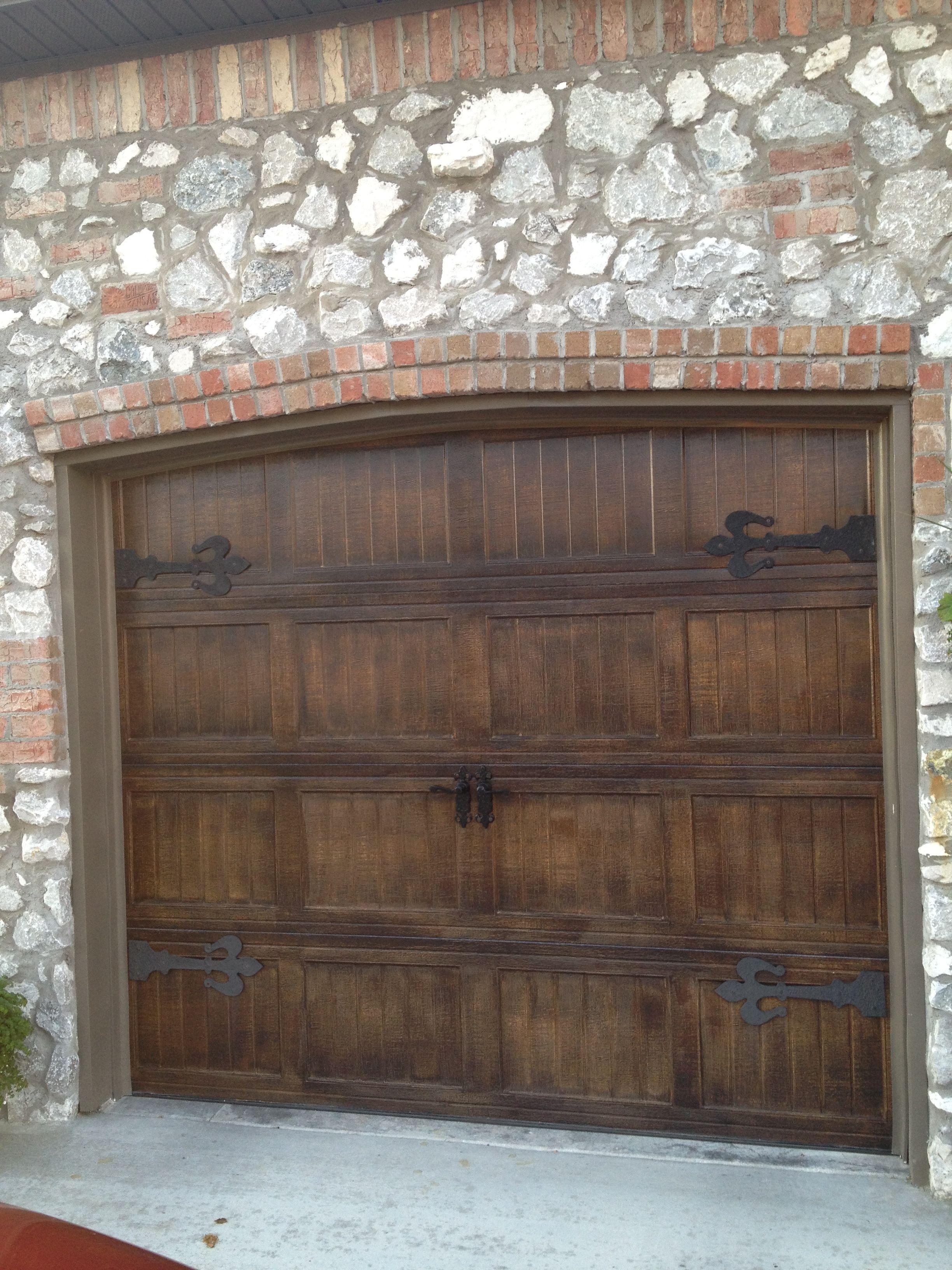 Metal garage doors painted to look like wood with fluer de for Garage doors wood look