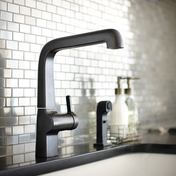 The Evoke Kitchen Faucet in Matte Black looks spectacular against the stainless steel subway tiles. Click through to see more!