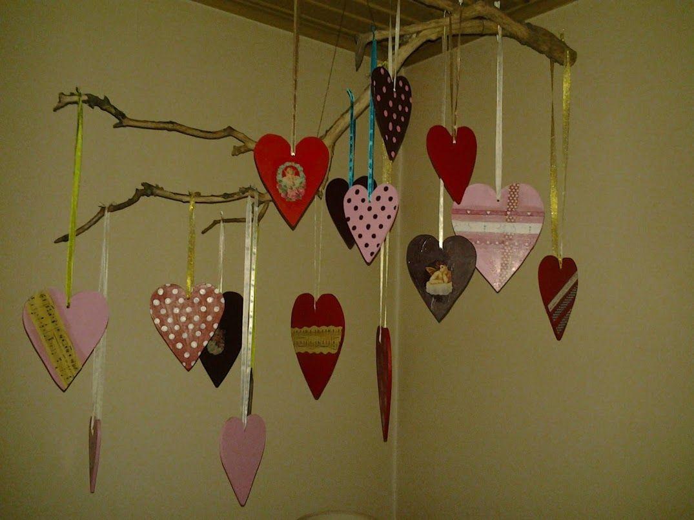 Malede træhjerter i forskellige størrelser, pyntet med glansbilleder, papirklip og bånd.