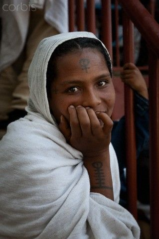 Ethiopian girl with a coptic cross tattoo on her forehead for Cross tattoo on forehead meaning