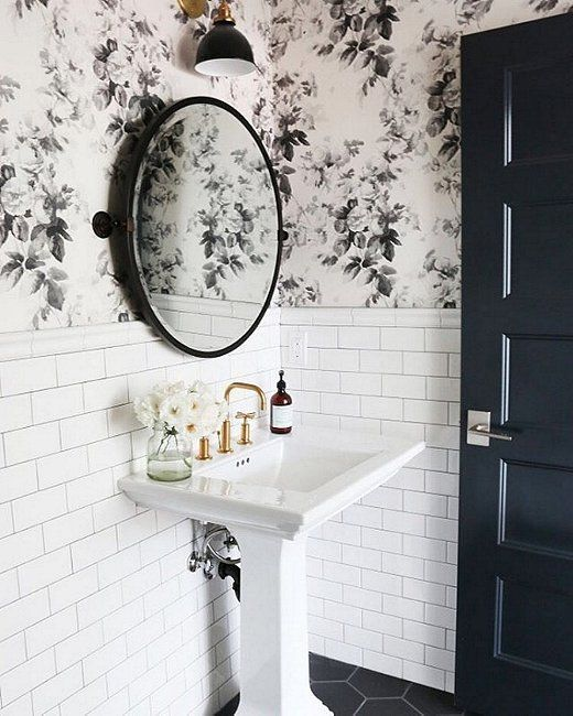 Love the floral wallpaper, brass sink faucet and industrial wall sconce in this monochromatic black and white bathroom!